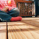 Child sitting on a wooden porch